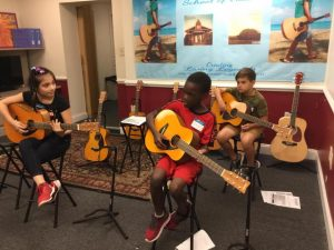 Children learning to play guitar